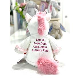 The back of the white unicorn with a embroidered message in hot pink.